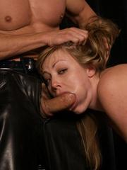 Blonde female is restrained to a bondage horse and made to suck cock
