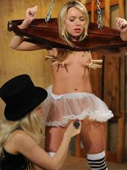 Blonde chick in a top hat tortures a blonde chick wearing a collar restraint