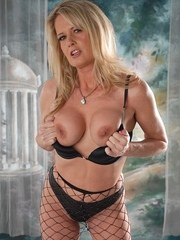 Older blonde lady Bridgett Lee removes her long black gloves and mesh hose