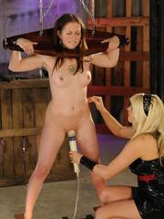 Blonde dominatrix subjects a female in a bondage collar to extreme pain