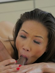 Older Asian woman Kalina Ryu takes the ball sac in her mouth during a blowjob