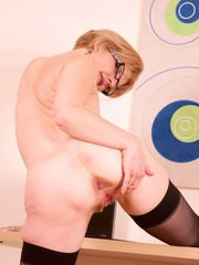 Older lady in glasses parts her pussy lips after stripping down to her nylons