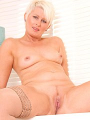 Older lady Sally Taylor masturbates after stripping to tan nylons and heels