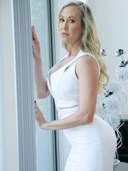 Mature lady Brandi Love unzips her dress on her way to posing naked
