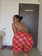 Topless Indian woman begins to pull down her shorts and underwear