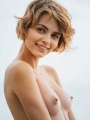 Fresh faced beauty with a perfect ass models naked on oceanside rocks