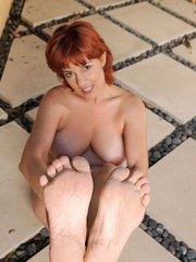 Older redhead peels off her lingerie and white nylons on the patio