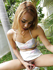 Blonde Asian tranny jerking off uncut cock outdoors for cumshot