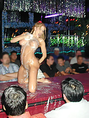Busty blonde slut Gina Lynn strips and poses for the camera on the cobblestone