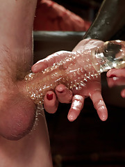 Maitresse Madeline covers slaves cock with a cock extending cock sheath fucks it