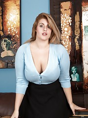 Ellie Roe stands in her blue blouse showing off her 36F breasts and legs in her black