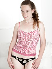 The all-natural Ana Molly poses in her pink top and denim shorts by her white sofa.