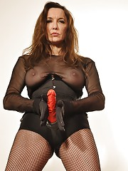 Gorgeous Femdom Strapon Jane is posing in fishnets with her favourite big red strapon