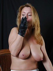 Busty Milf Kelly smokes her cigarette nice and slow wearing her soft leather gloves
