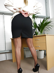 Blonde secretary in seamed stockings shows her secrets in the office.