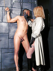 Sexy blonde dominatrix wearing leather gloves ties up her submissive and plays with