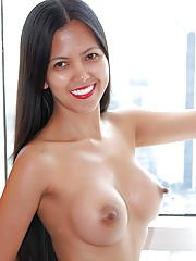 Slender sexy Filipina with fake tits strips nude by window