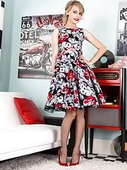 In a full skirted frock brown fully fashioned nylons and red patent leather sling