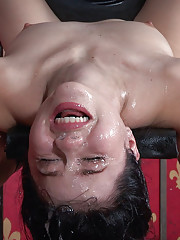 Bound on her back her legs spread and head hanging over the edge of a table Yhivi