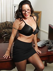 Busty older secretary Desire Delgoto strips naked.