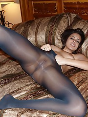 Nina James is on her bed wearing a black crotchless body-stocking and she holds her