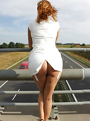 A daring photoshoot! Standing over a highway bridge Vixen lifts her skirt and flashes