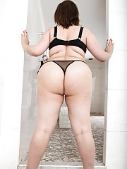 BBW brunette in sexy black lingerie covers a guy in her fat