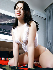 Sivilla strips on the bed baring her creamy white body and smooth pussy.