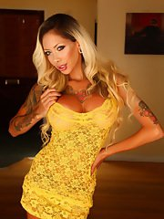 Busty tattooed babe Chanel shows off her huge tits in a skimpy yellow lace outfit