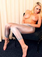 Big breasted young blondie strips her shiny nylons for you