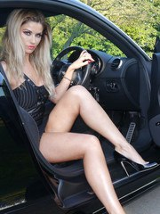 Gorgeous leggy blonde Kathryn is behind the wheel of a powerful Audi sport car in