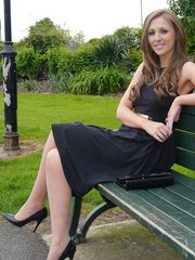 Sexy brunette Debbie takes a stroll into the park in a pretty dress and gorgeous