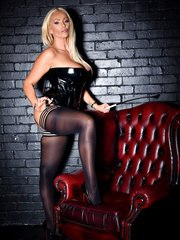 Strict Mistress Lucy Zara is in a domination session wearing latex and whip in hand