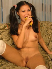 Petite schoolgirl shoving a banana into her pussy before eating it
