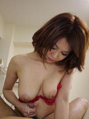 Erika Nishino with cans out of red bra strokes penis to get cum