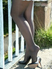 Gorgeous blonde Erin is outdoors showing off her shiny legs covered in silky nylon