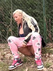 Funky looking blonde squats to piss while outside