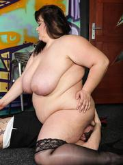 Fat meloned brunette BBW in stockings sits on a guys face