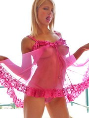Blonde slut Monica removes her pink sheer lingerie to reveal her perky tits