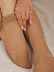 Kym hikes up her short black skirt to reveal her pantyhosed legs and feet.