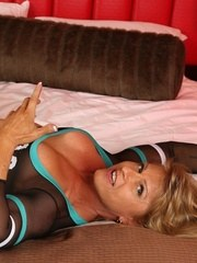 Bodybuilder Emery Miller rolls around the bed strips and flexes her huge muscles.