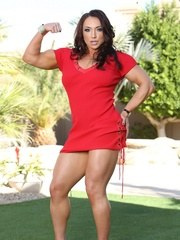 Brandi Mae stands outside in her sexy red dress flexing all her strong powerful muscles