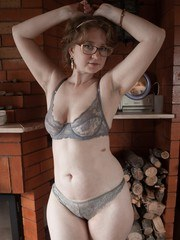 Bazhena is relaxing by her fireplace and stripping off her dress lingerie and stockings.