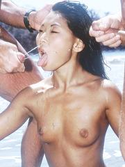 Young asian girl takes on two cocks at a tropical beach