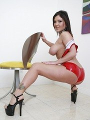 Busty slut Claire Dames poses in red latex in the hot solo set