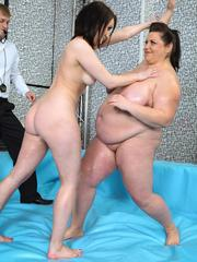Oiled brunette BBW wrestling with a skinny girl with her toy