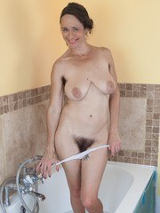 Josie is taking a bath and wearing her white top and panties before getting in. She