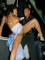 Wet club babes sharing a large dick on their knees in public