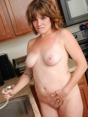 Jen sprays her tits down in the kitchen