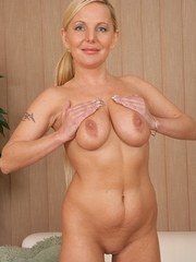 Busty blonde babe Alena shows off her smooth shaved pussy.